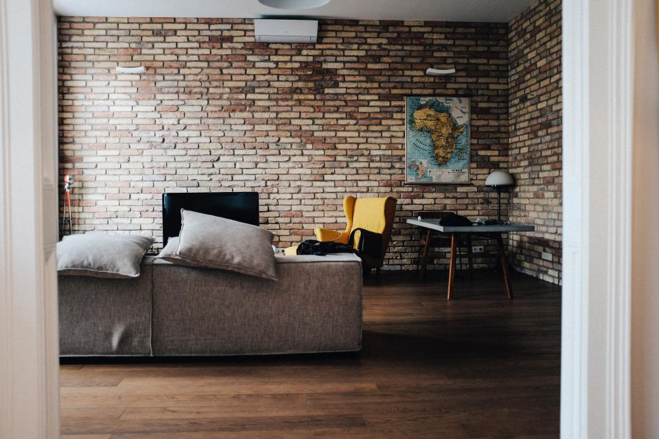 house interior couch sofa living room brick wall