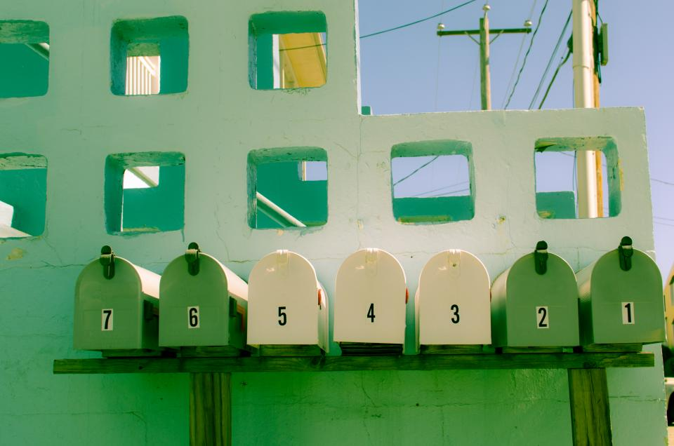green mailbox yellow numbers letters wall
