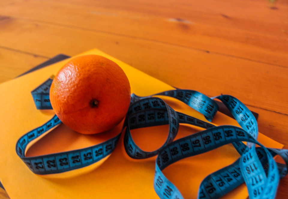 orange fruit healthy food measuring tape paper table