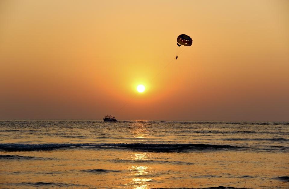 sea ocean water waves nature horizon orange sky cloud sunset boat sailing silhouette parachute adventure sun reflection