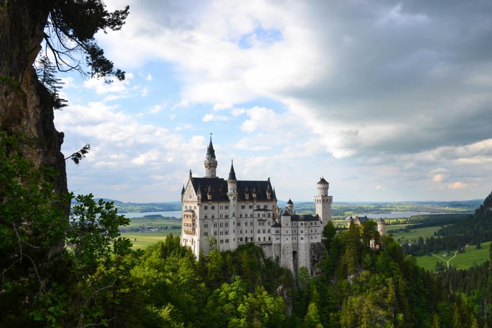 neuschwanstein castle landscape trees leaves clouds terrain lush picturesque