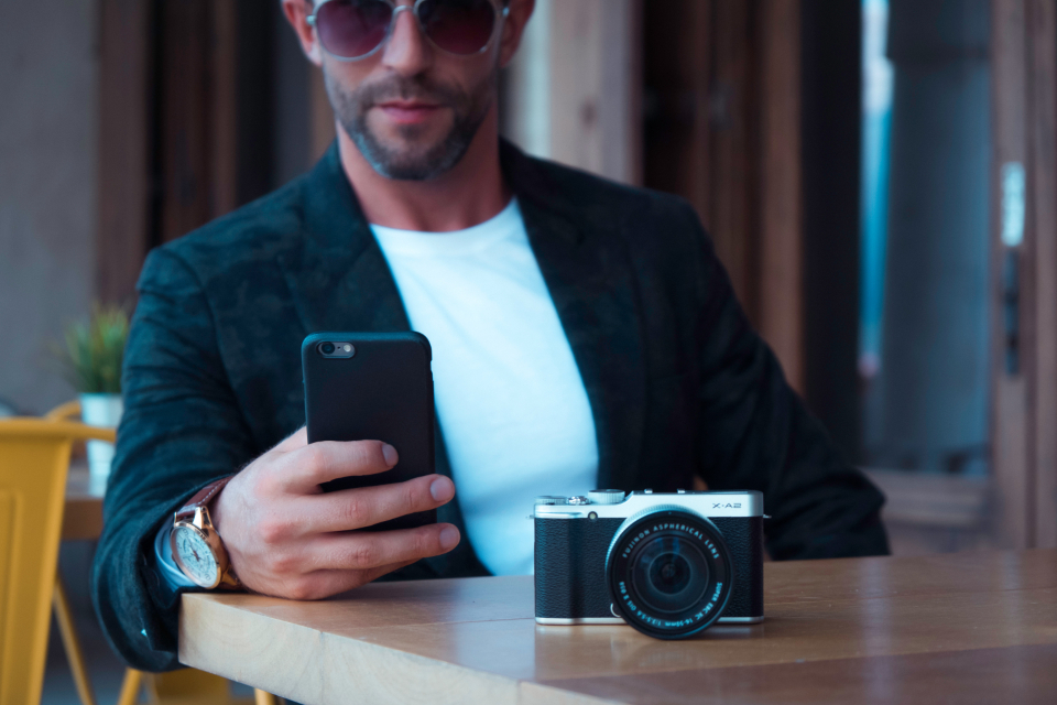 man camera mobile phone technology pose sunglasses table bar watch wait dslr photography photographer device telephone