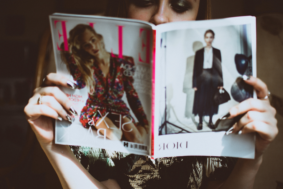woman reading fashion magazine female girl elle vogue learn relax hands hold