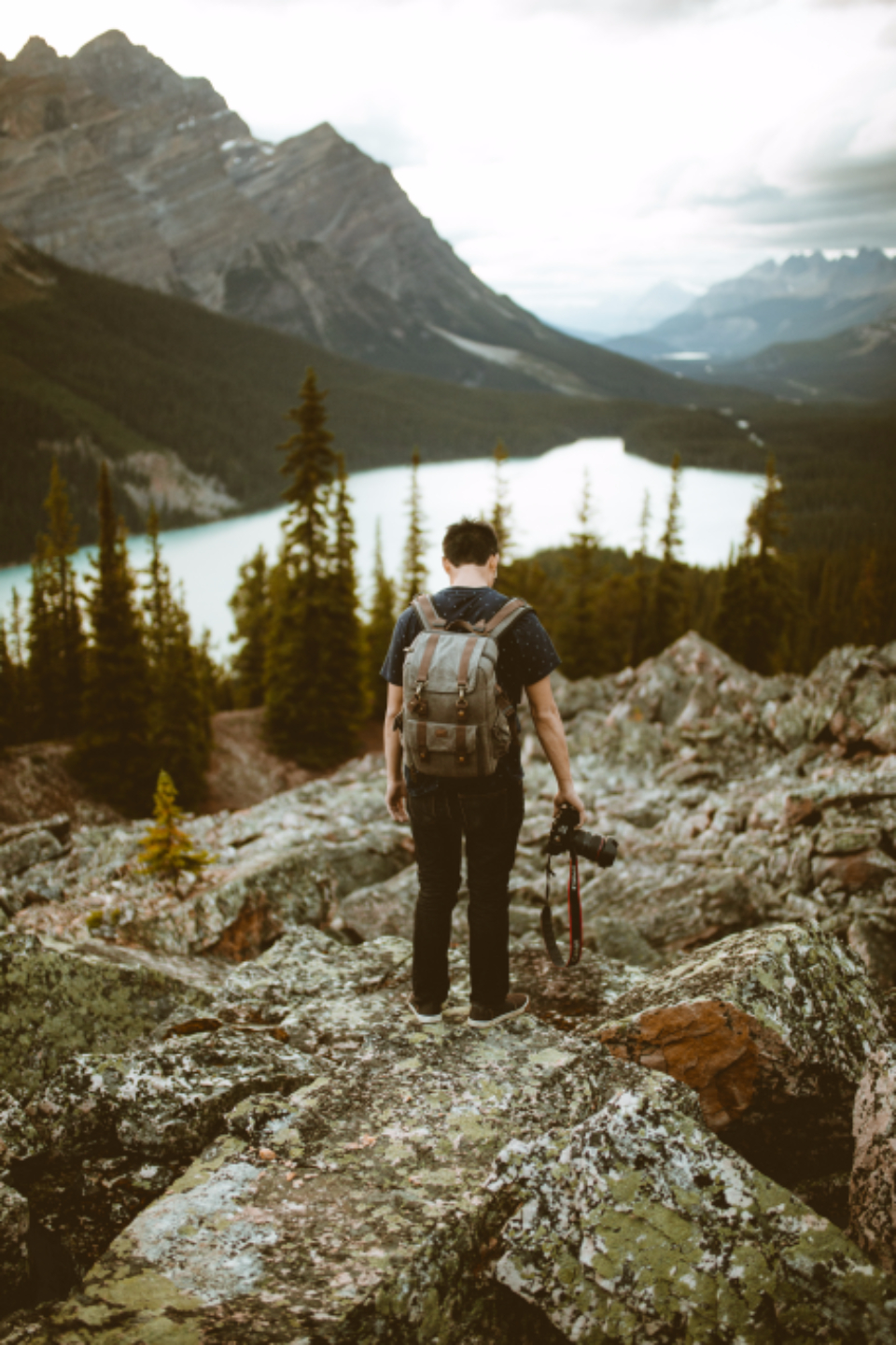 Boy guy man male person people lake nature earth sky rocks mountain mountains Pyeto Alberta photographer photograph photo camera Canon lens backpack asian Chinese