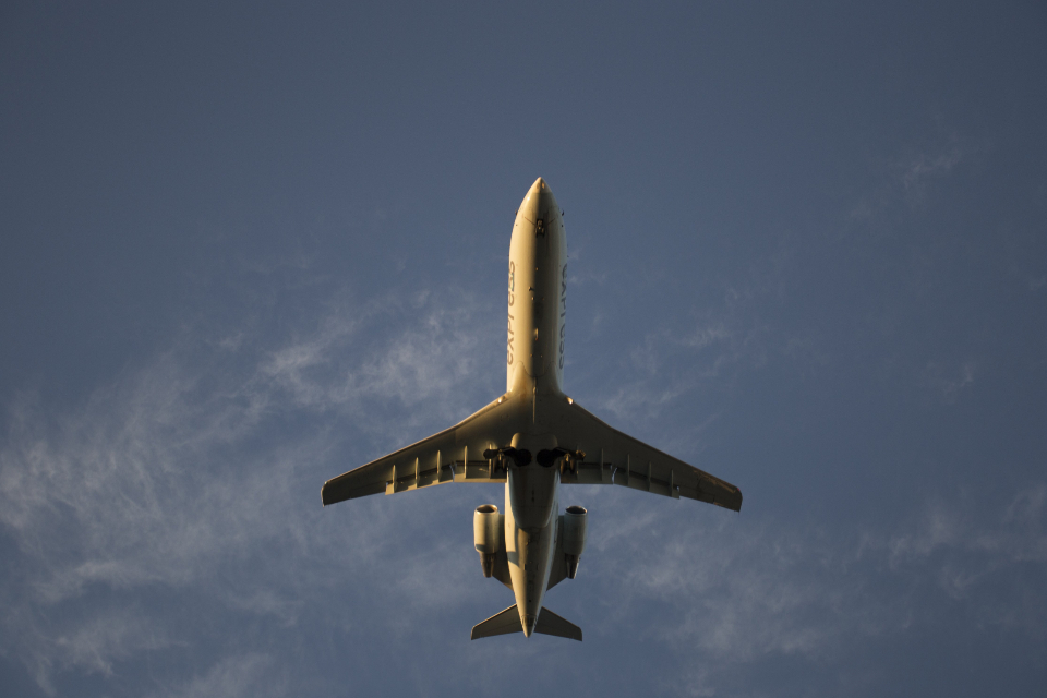 low flying plane sky blue travel flight above air jet landing take-off wings engines travel transport sky
