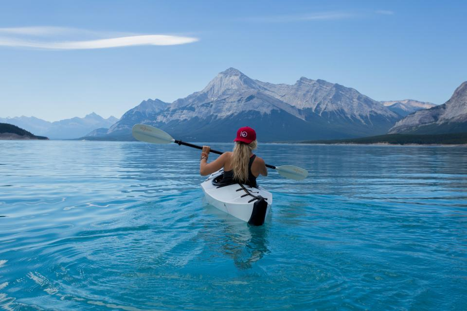 woman girl lady people back snapback cap kayak paddle nature landscape mountains peaks summit sea ocean water ripples sky clouds horizon blue fitness