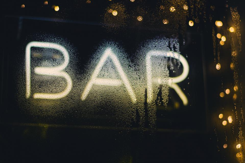 bar establishment window wet droplets water liquid lights signage glass restaurant liquor food drinks