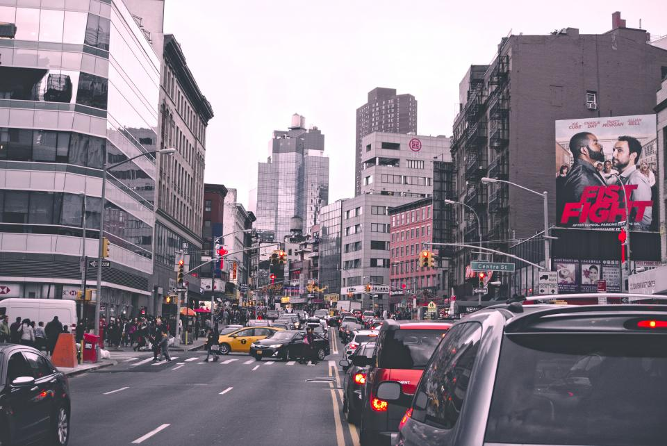 city buildings structures architecture pedestrian crossing car vehicles taxi transportation road street billboard traffic lights skyline urban outdoors travel