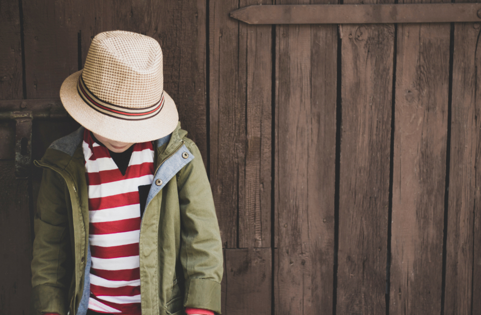 young child hat stripes red white jacket coat wood panel thought think boy male family