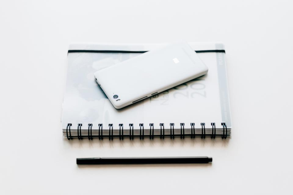 black and white notebook pen mobile phone smartphone gadget touchscreen electronic technology white work desk table business office