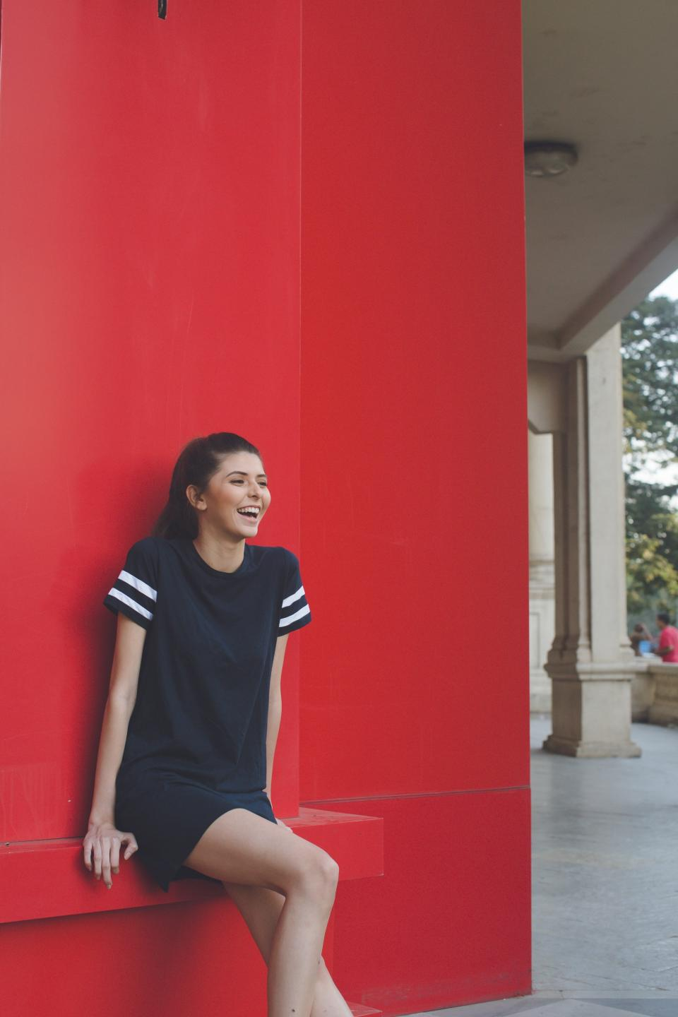 people girl woman smile happy alone red wall building outside