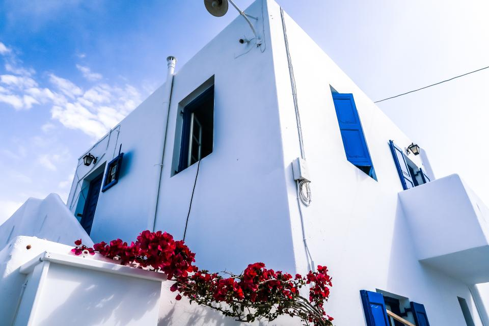 architecture white building infrastructure blue sky cloud red flowers outside
