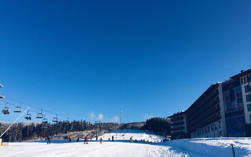 skiing glide people man woman children trip vacation adventure snow winter adventure white sky nature tree pine building establishment hotel clouds