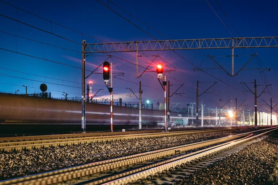 railway railroad train tracks transportation lights night evening dark power lines