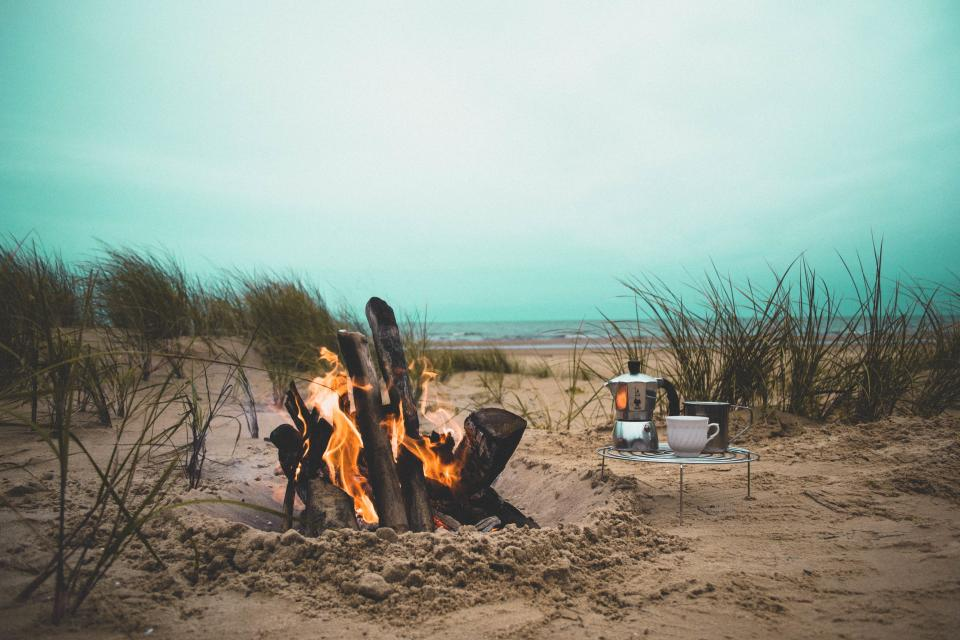 fire flame bonfire campfire beach heat firewood grass sand kitchenware picnic sea ocean water coast shore travel vacation relax horizon clouds sky