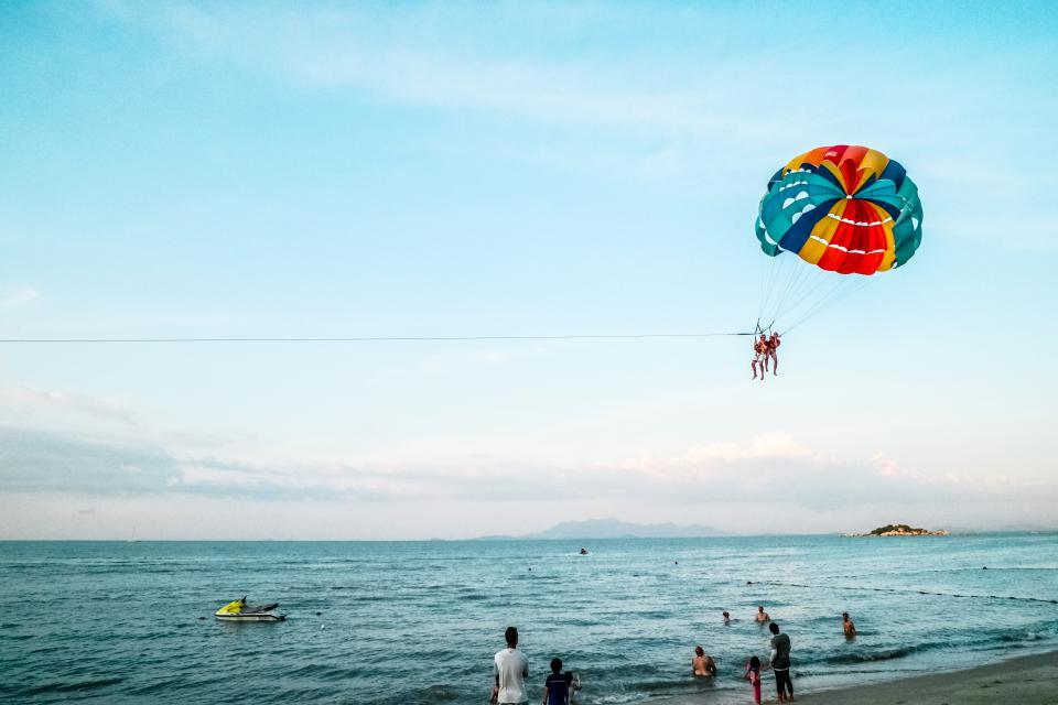 crafts hobby paragliding nature beach shore sand water ocean sea waves jet ski people sky clouds horizon