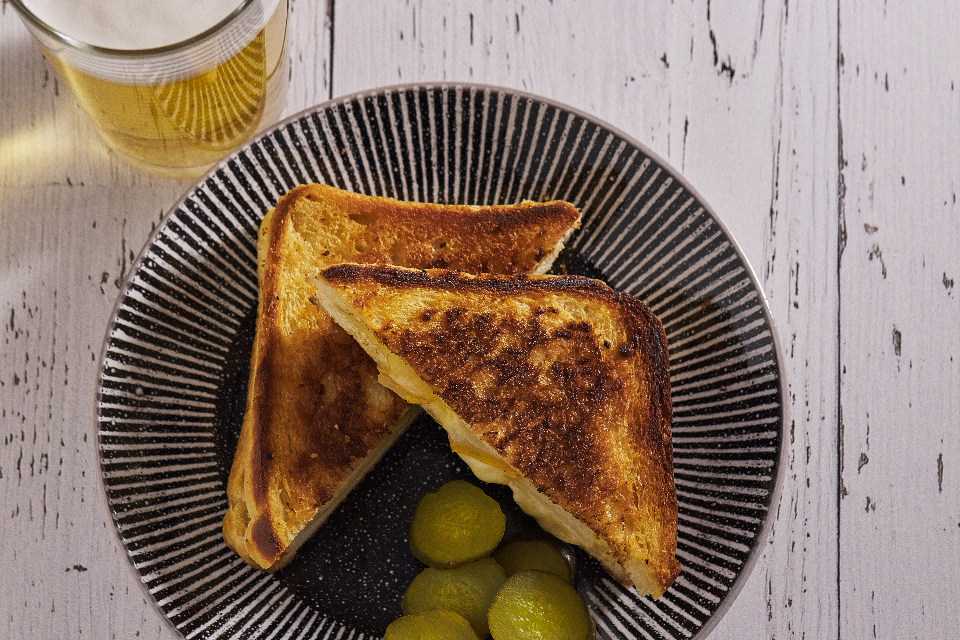 grilled cheese sandwich top view melted toasted bread plate pickles beer food snack lunch homemade