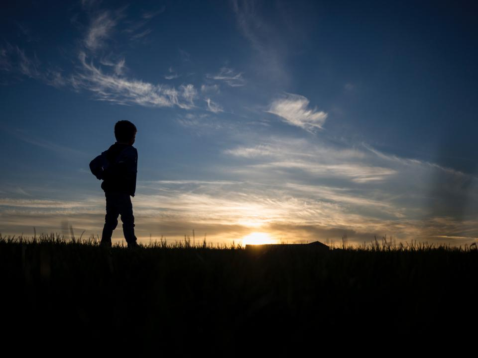 people kid boy standing alone sunset blue sky cloud silhouette landscape