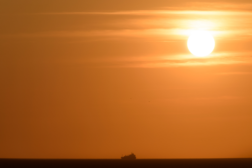 ocean sunset ship sea boat warm golden horizon silhouette sky view water landscape seascape nature transport