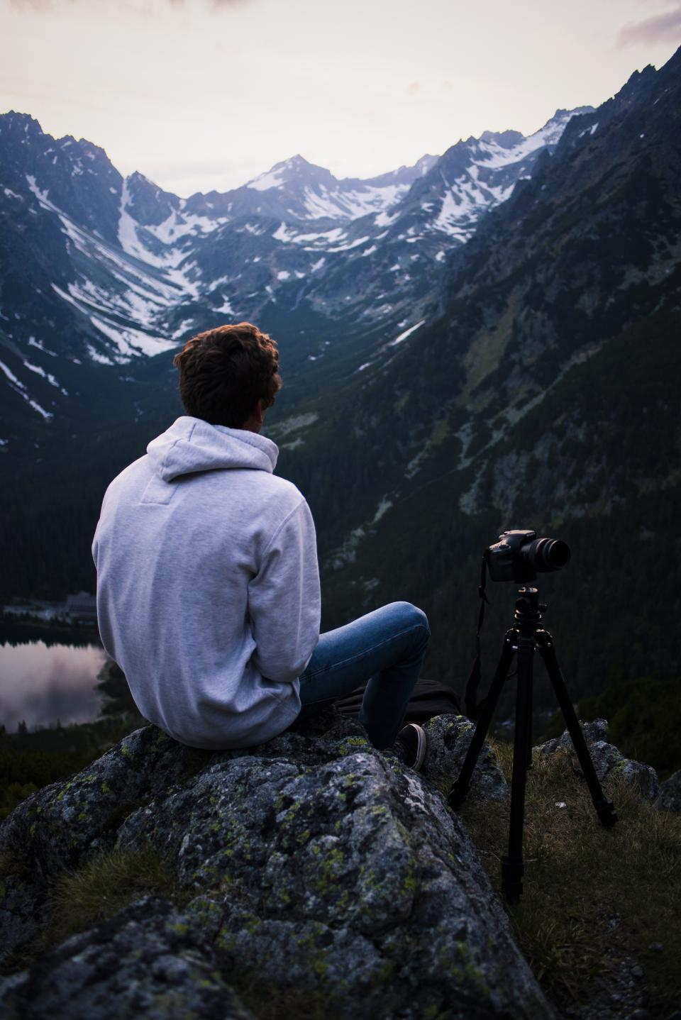 guy man male people back contemplate nature mountains rocks snow travel trek hike climb summit peaks fog vegetation grass trees rocks sky horizon water lake sea reflection tripod dslr camera photography