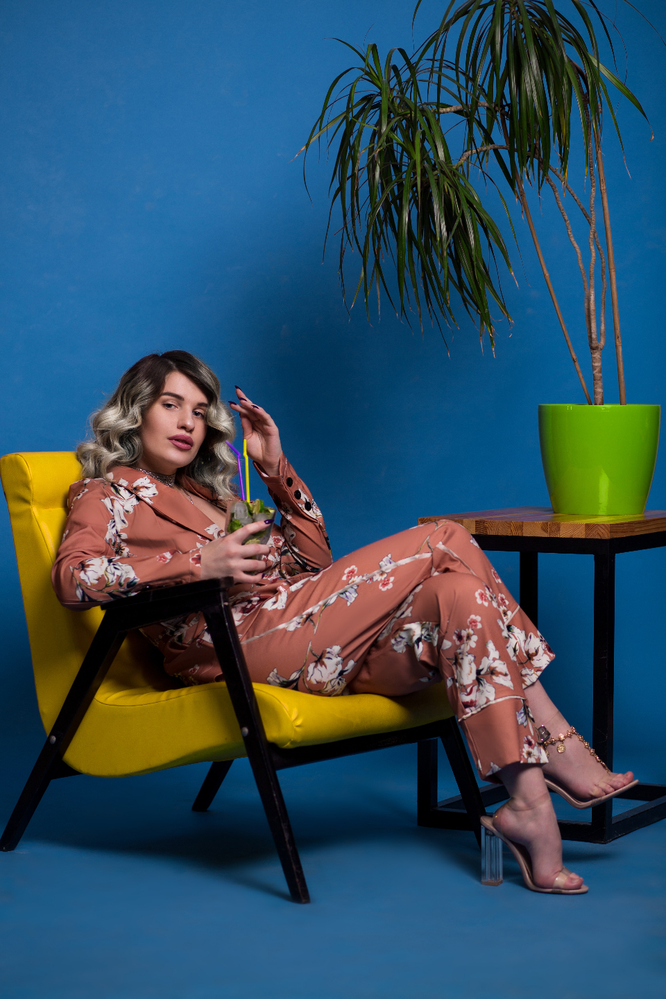 cool woman chilling cocktail yellow chair blue wall green vase plant highheels headphones drink straw