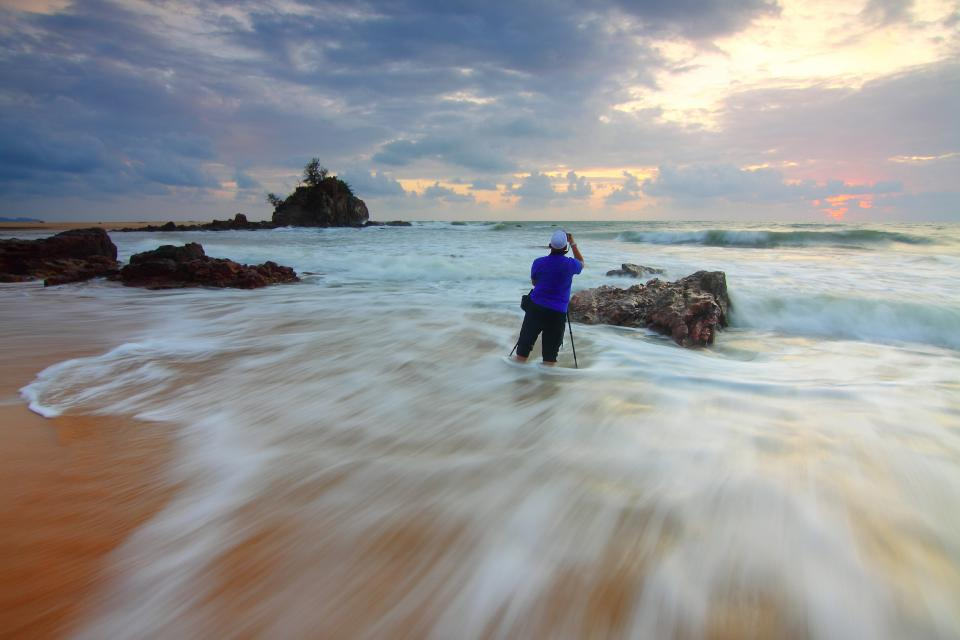 sea ocean water waves rocks formation sand beach people man photographer photography clouds sky