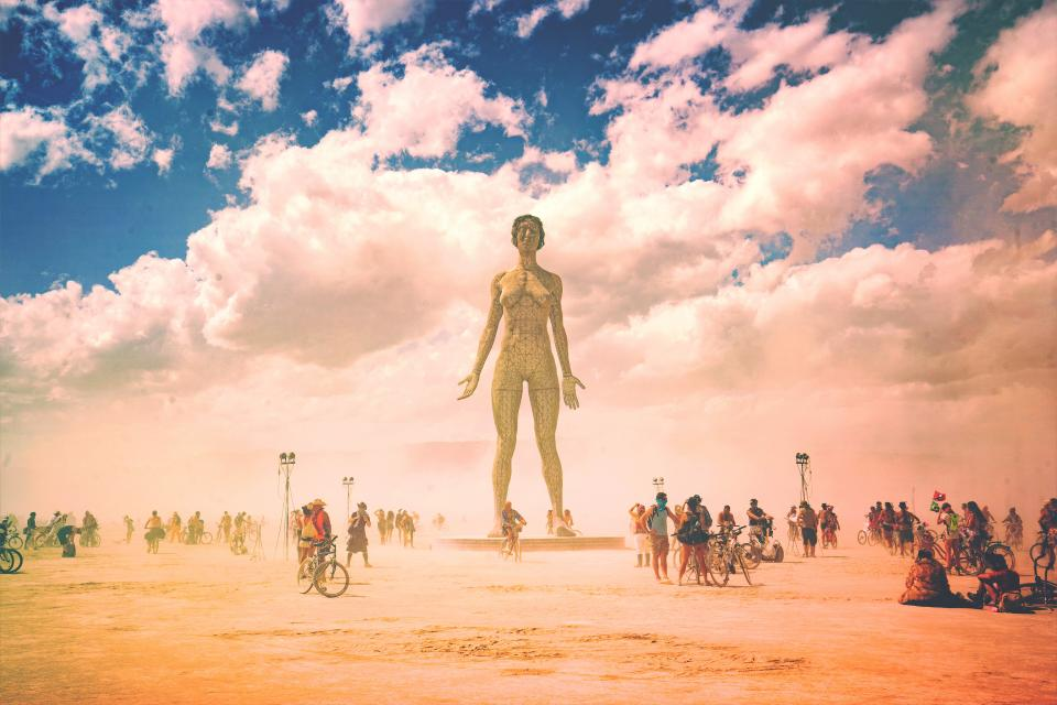 people crowd group friends family statue blue sky clouds bike bicycle men women