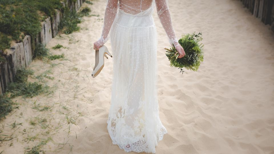 woman girl lady people bride wedding gown bouquet shoes sand wood fences lush vegetation beauty