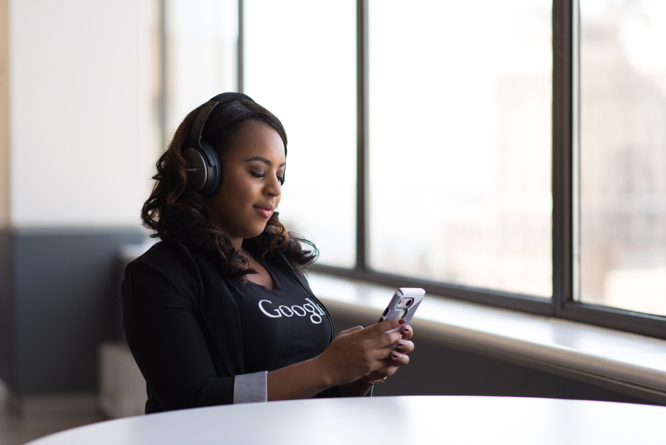 woman headphones mobile device computer work google t-shirt desk office business african american people