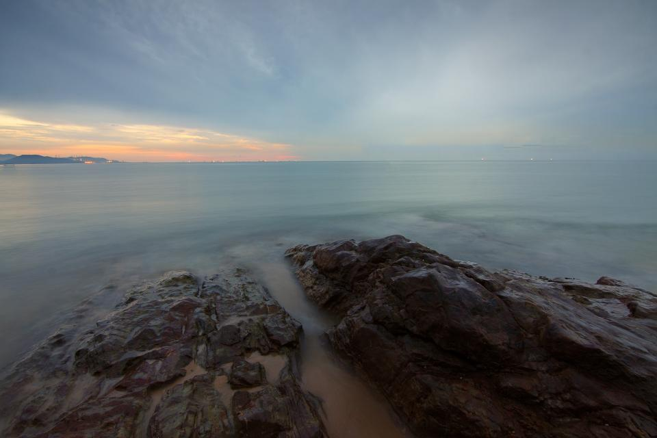 sea water rocks horizon clouds sky sunset nature ocean