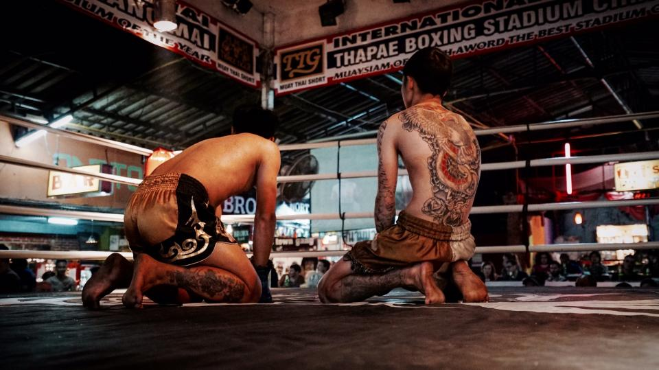 boxing ring men guys people tattoos sports lights gloves signage roof shorts back tired