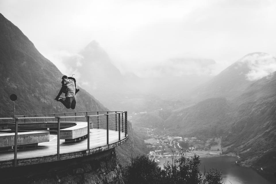 guy man jumping lookout railing view people lifestyle mountains hills cliffs landscape nature river clouds black and white