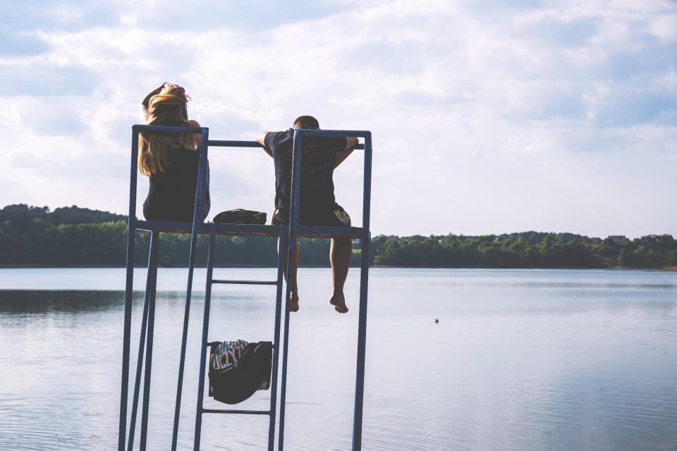man woman people couple friends love affection date sit water lake river view sky clouds horizon