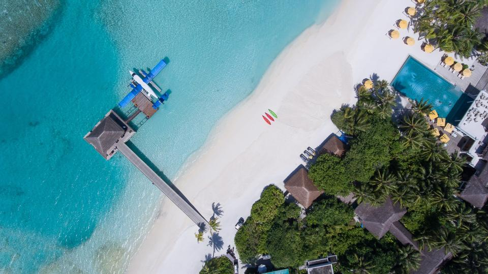 aerial land water ocean sea green blue house beach sand ocean sea surf waves trees vacation trip travel