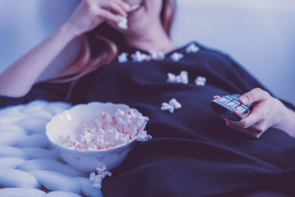 woman eating popcorn blond smile happy television tv remote control remote spill bed