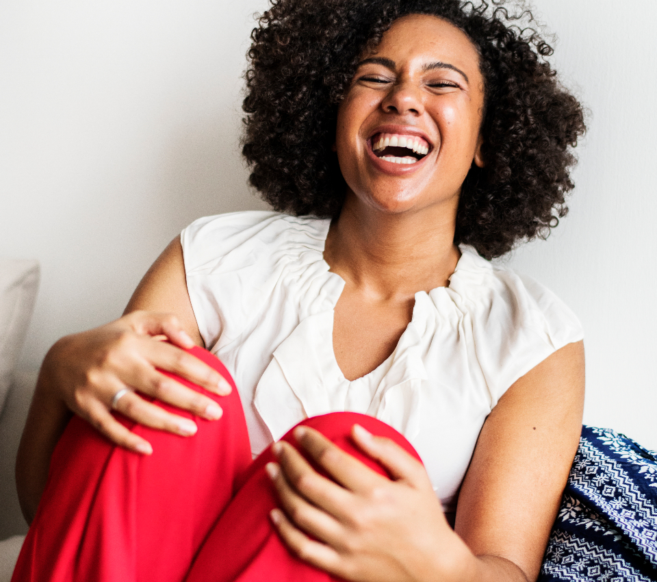 adult african american amused beautiful big hair black break bright chilling colorful comedy couch curvy cushions eccentric emotional enjoyment expressive fashionable gorgeous happiness happy heartwarming home hugging humor