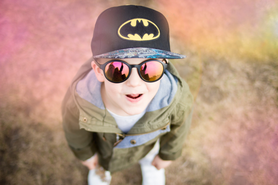young boy batman hat child superhero cap bokeh effect sunglasses reflection people