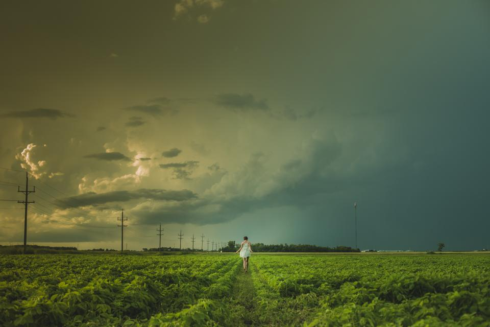 girl woman field grass nature landscape sky clouds cloudy storm power lines people green dress