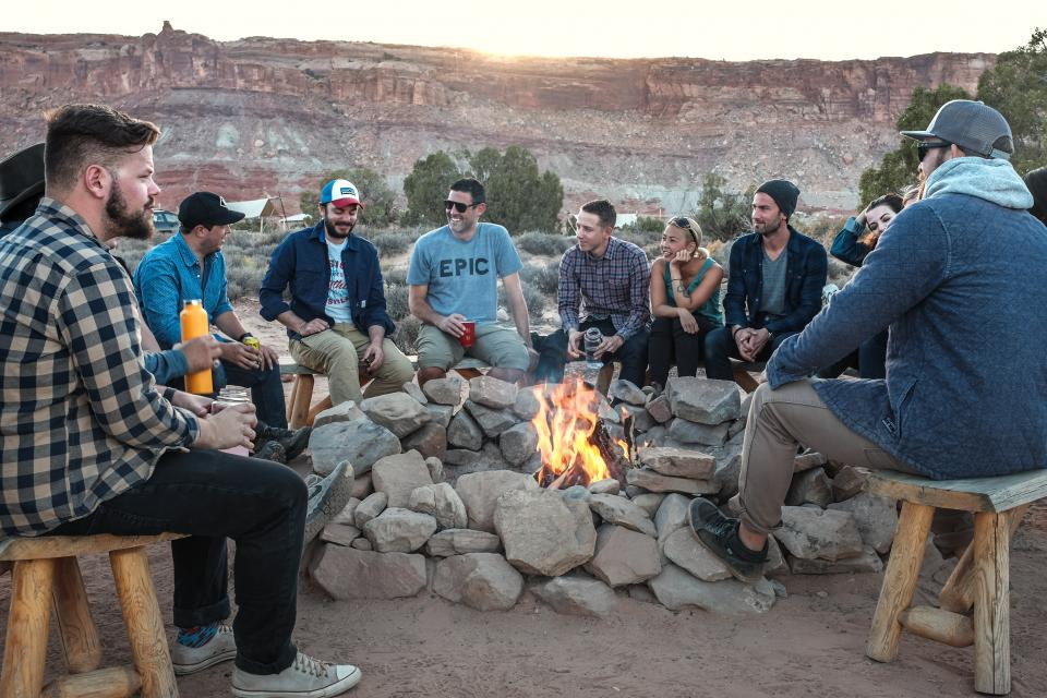 people men fire flame camping rocks wooden bench women smile laugh happy group friends