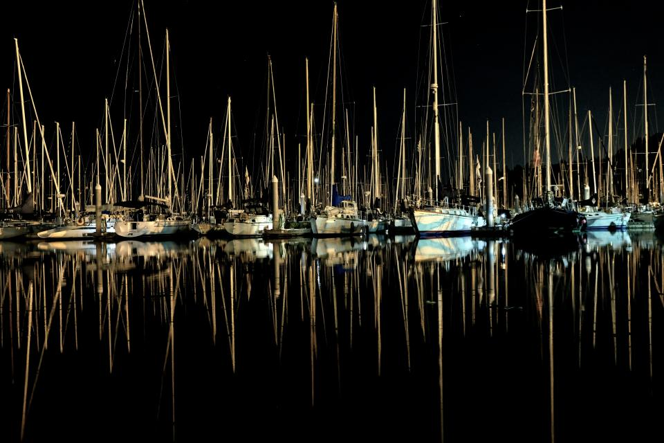 reflection dark night sea water lights yacht