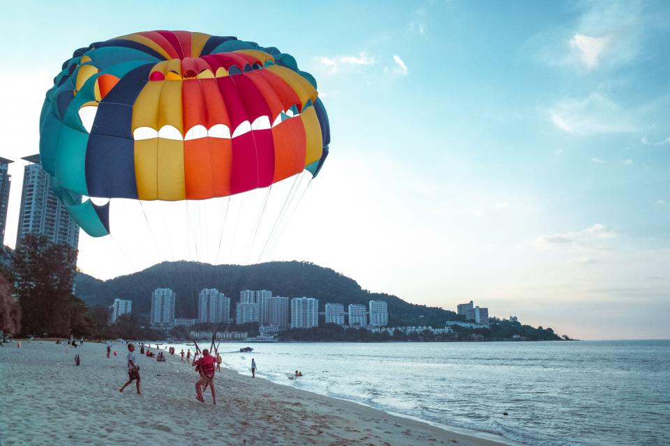 nature beach shore sand water ocean waves splash paragliding parachute people buildings resort mountain slope sky clouds horizon