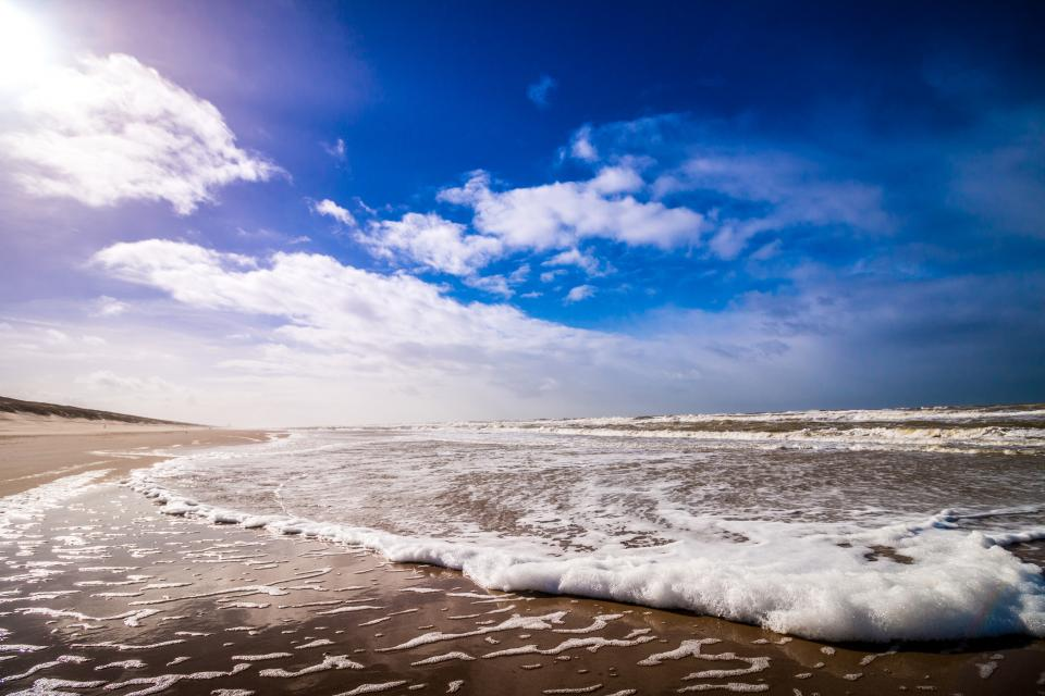 nature coast beach shore water ocean sea waves splash bubbles froth sky horizon clouds