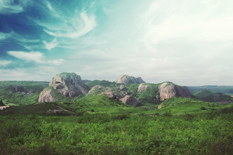 green grass field rocks boulders landscape nature sky clouds sunshine