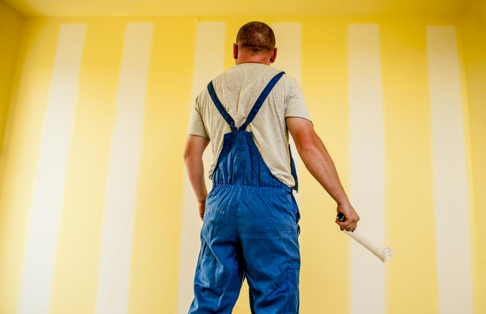 guy man painting brush roller walls overalls work construction renovations repair room house home people