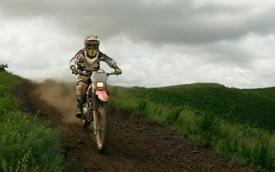 people man dirt bike adventure clouds sky gear helmet grass field green