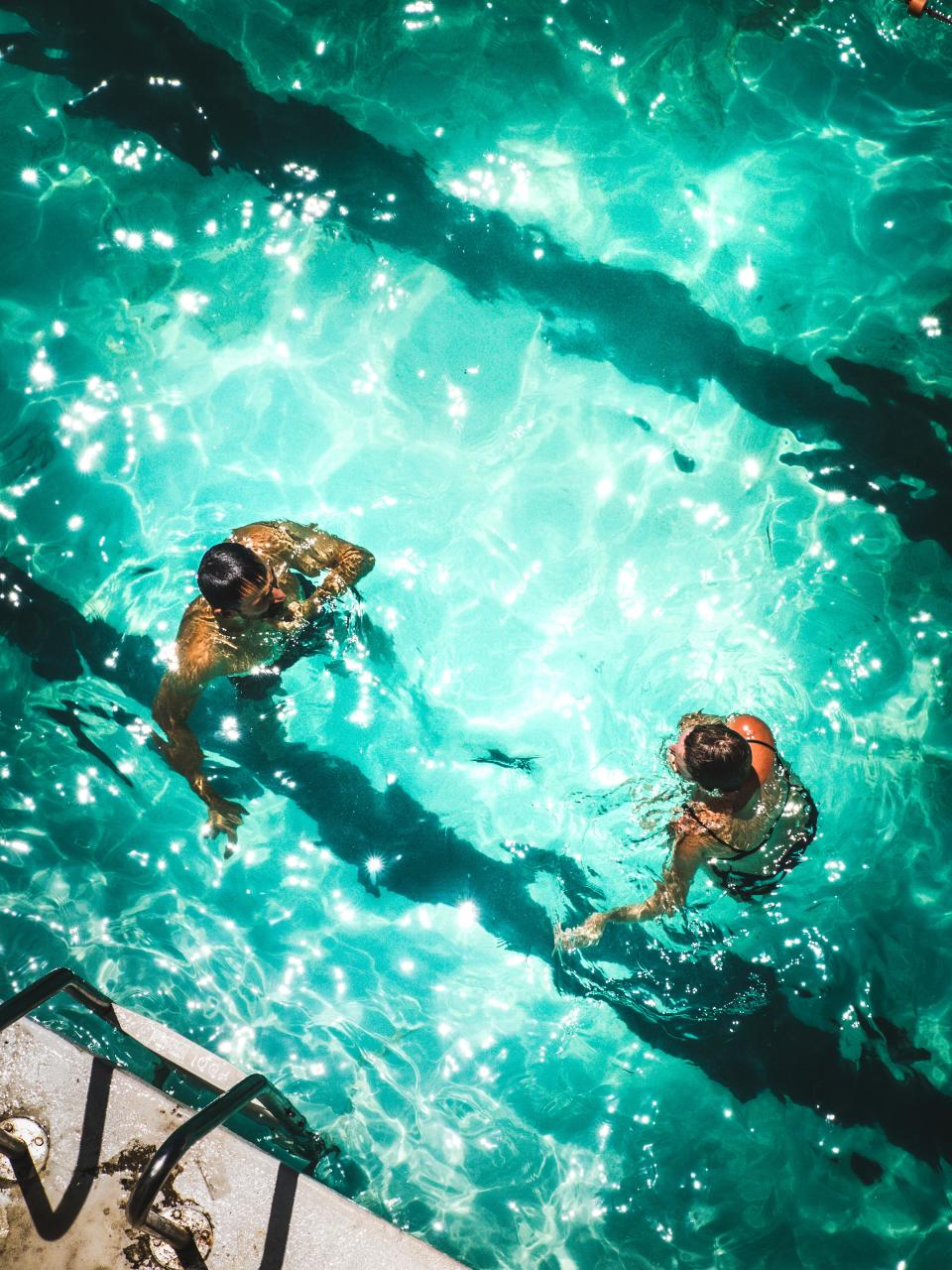 swimming pool blue water swim people man woman couple sunny day summer outdoor reflection