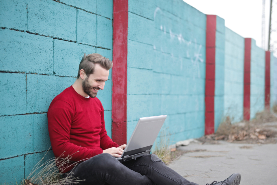 man laptop smile happy technology computer brick wall blue fashion red jumper jersey jeans