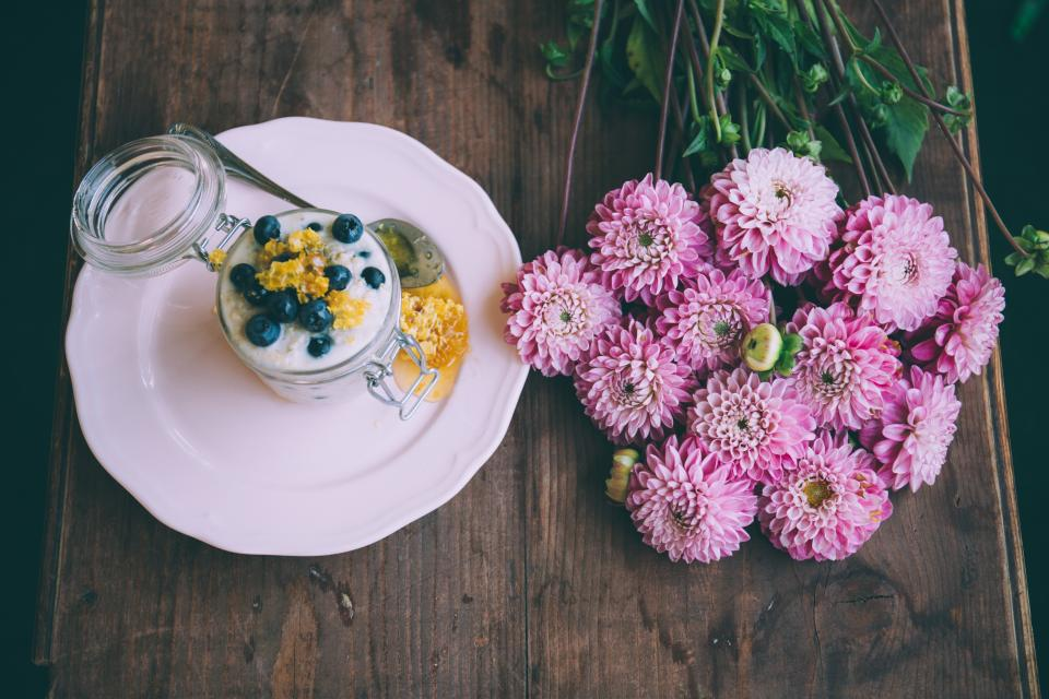 table wood brown flowers pink nature plant leaves petals dessert white plate spoon glass container blueberry