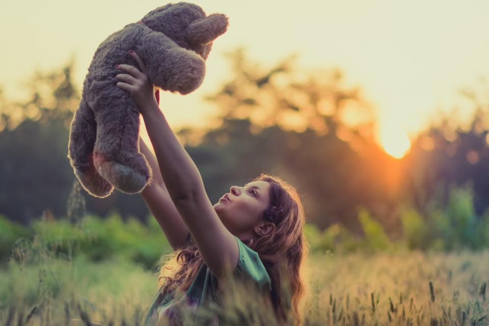 people girl teddy bear toy green grass field blur sunrise sunset nature