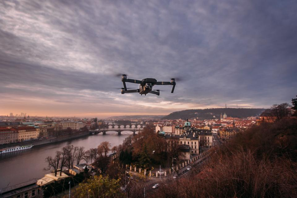 drone plants trees camera water river bridge building clouds sky video record mountain vehicles